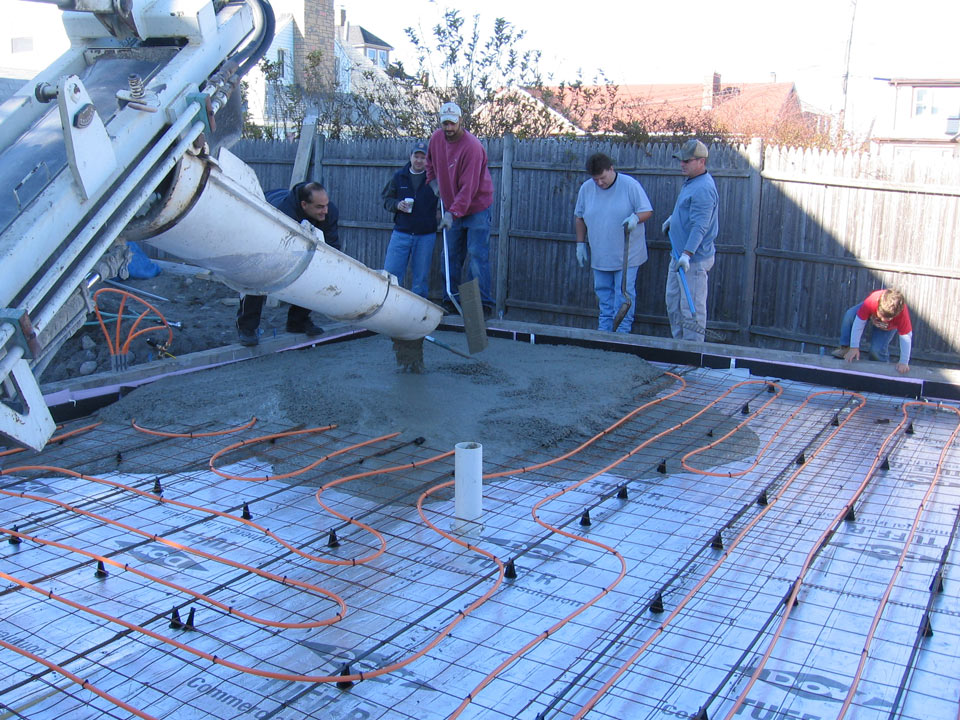 Pouring concrete over residential heat tubing